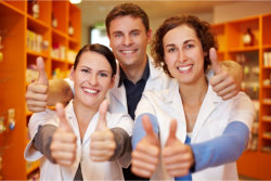 happy pharmacy team holding their thumbs up