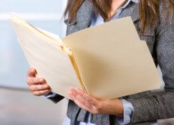 business woman holding legal documents in modern office